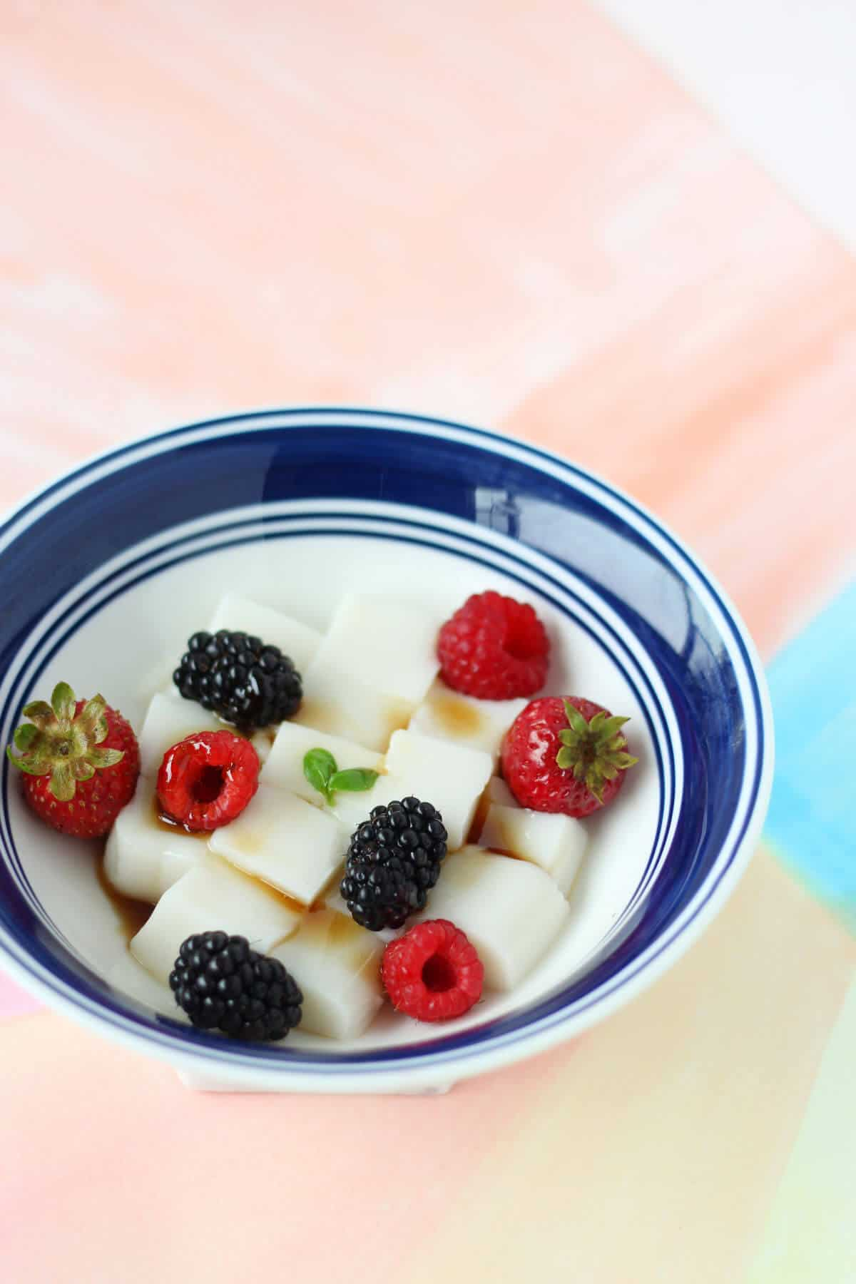 White bowl with blue rim, filled with cubes of white opaque almond tofu and topped with summer berries and brown sugar syrup.