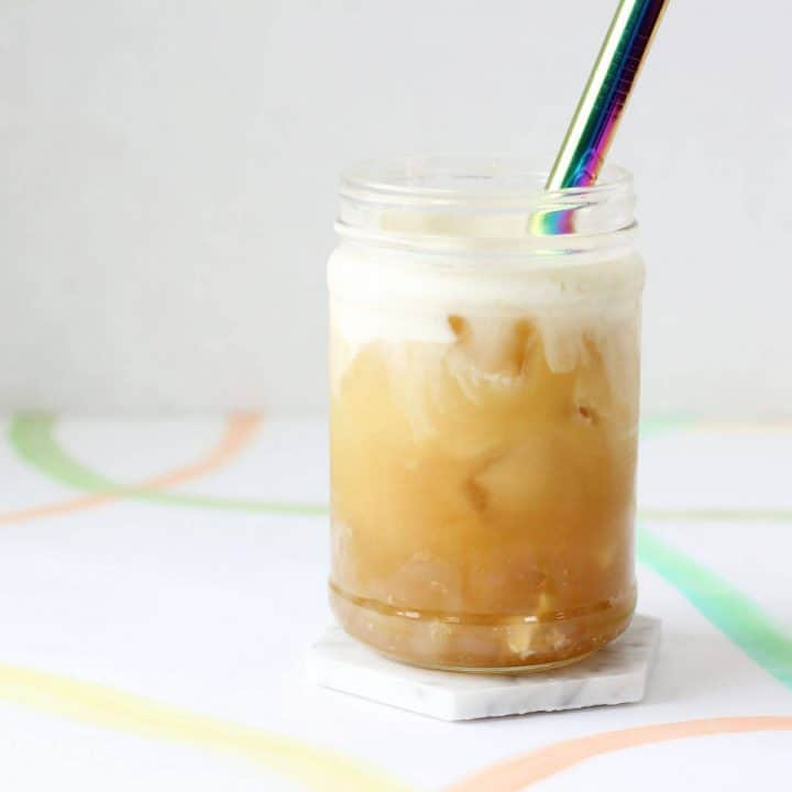 White coaster with clear glass filled with orange colored tea, ice, white cheese foam and a metal straw.