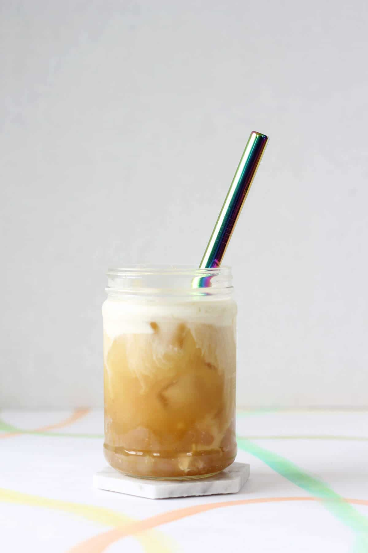 White coaster holding clear glass filled with opaque boba, orange colored iced tea, white foam and a metal straw.