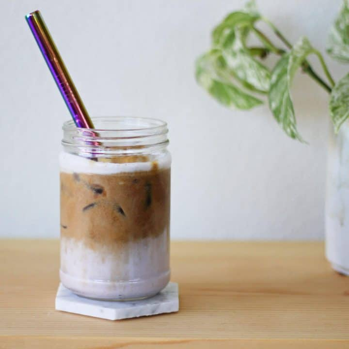 White coaster under clear glass with a layer of creamy lilac-colored taro milk topped with ice and a shot of espresso.