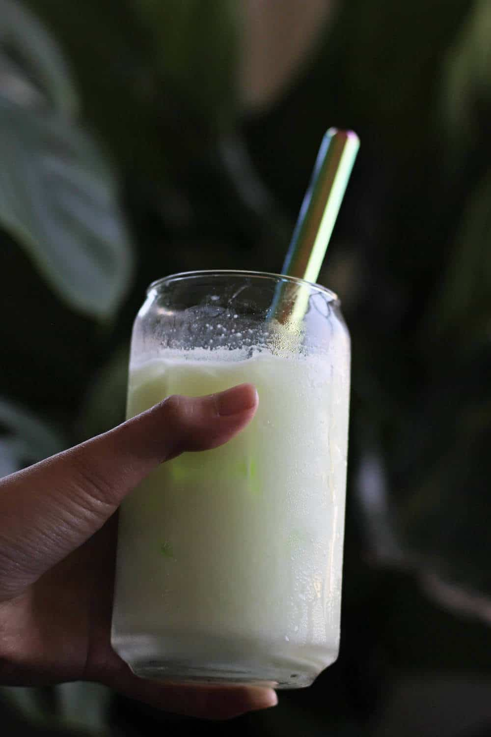 Hand holding clear cup filled with opaque, slightly green liquid and a metal straw.