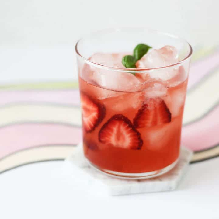Clear glass filled with pink cocktail, sliced strawberries, ice and a sprig of basil.