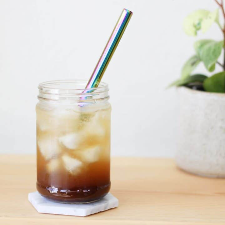 Clear glass filled with a shot of espresso and iced, then topped off with sparkling water and served with a metal straw.